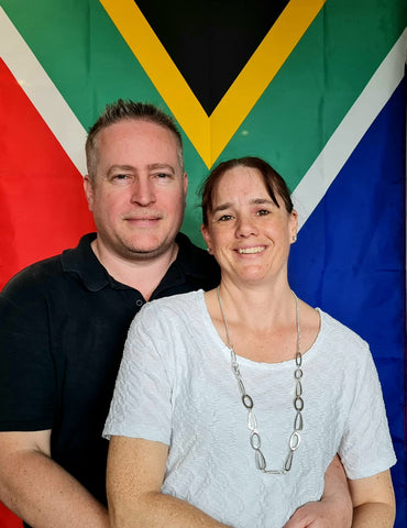Justin and Vanessa Smit the owners of The SAFFA Shack Hawkes Bay New Zealand posing in front of the South African flag.