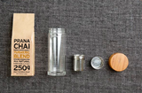 Flat lay Prana Chai Turmeric Blend & Glass Infuser Bottle