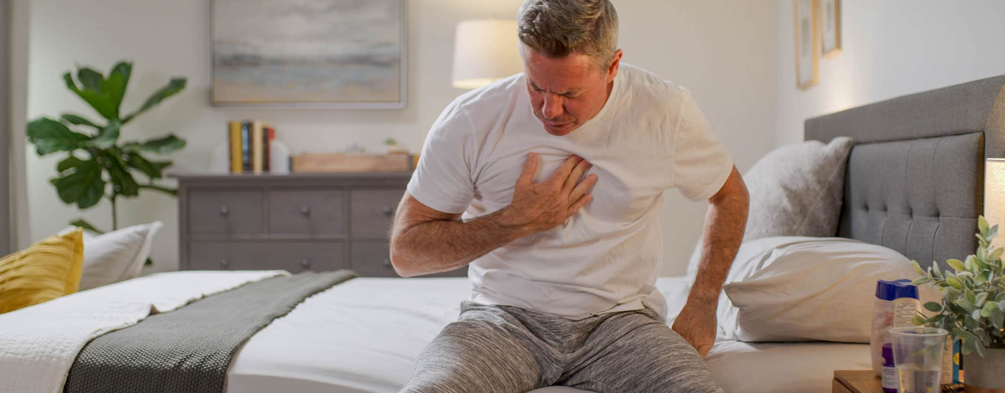 man on bed unable to sleep from reflux