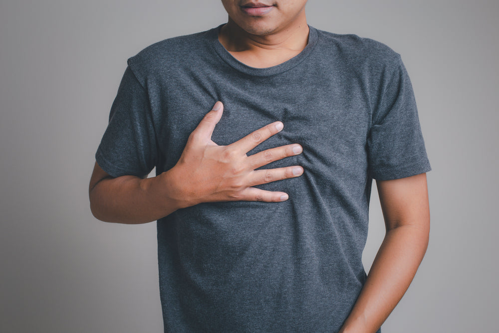 man holding chest from acid reflux pain