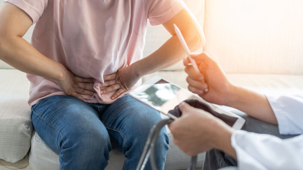 Patient sits with doctor and holds hands to stomach in sign of discomfort