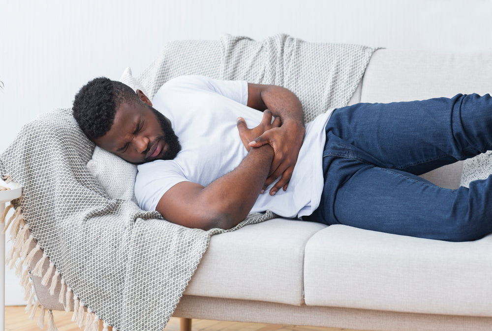 man laying on couch with heartburn pain