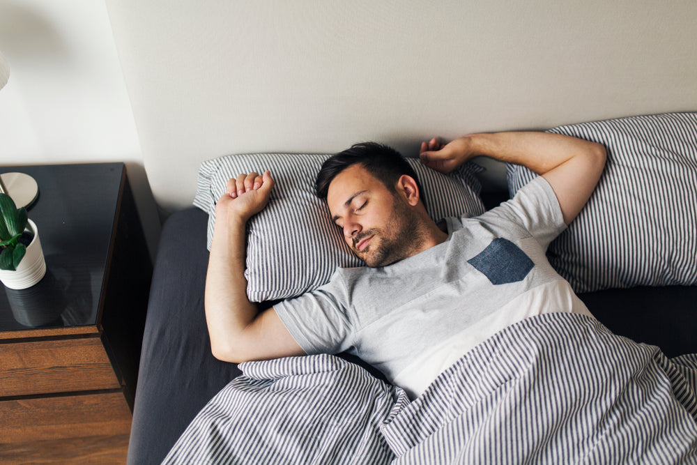 Man sleeps directly on his back with hands up near his head