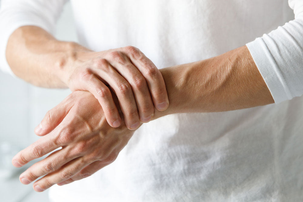 man suffering from arm numbness holding wrist