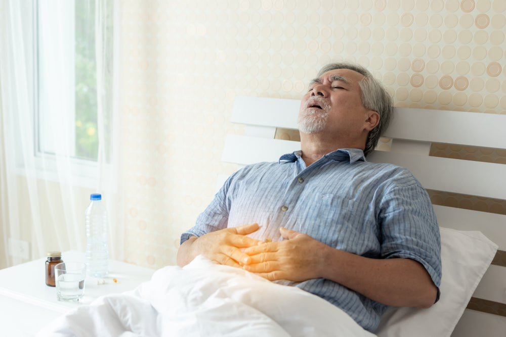 Older man in pain while lying in bed