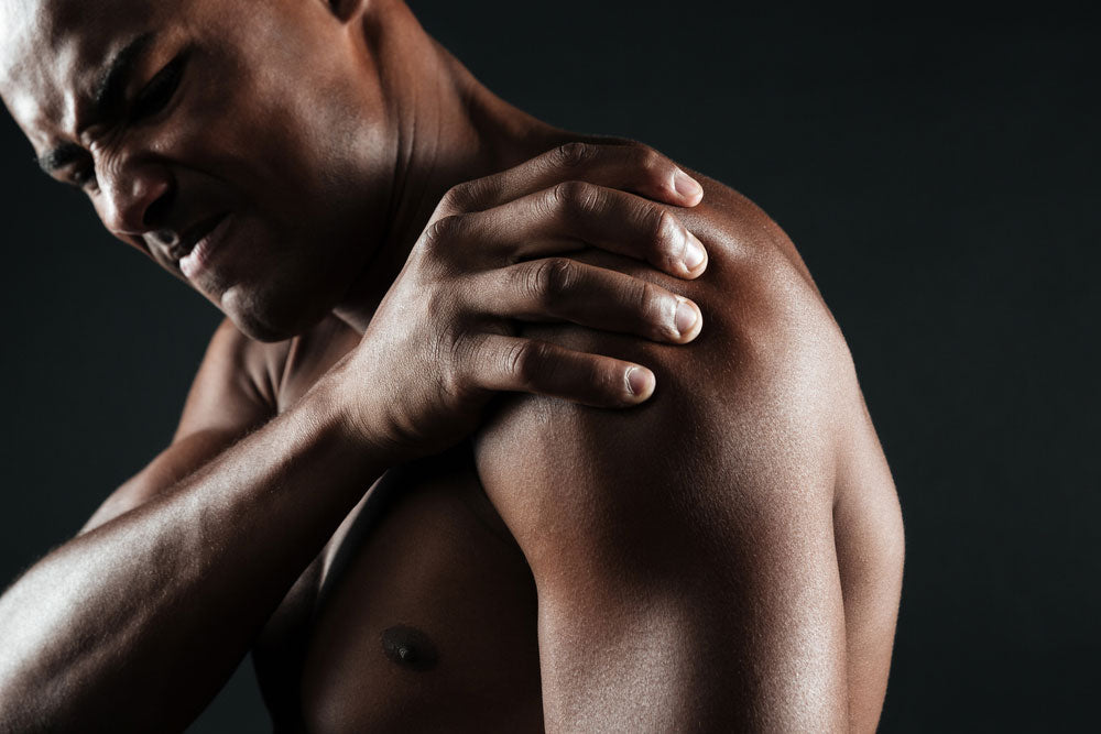 man in holding shoulder in pain
