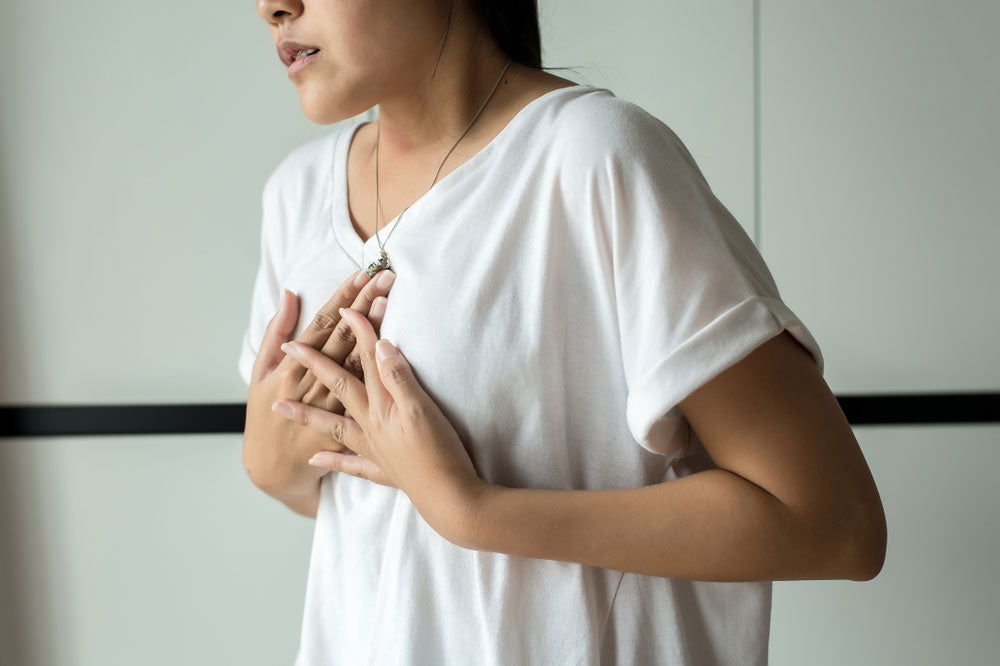 woman holding chest from GERD pain