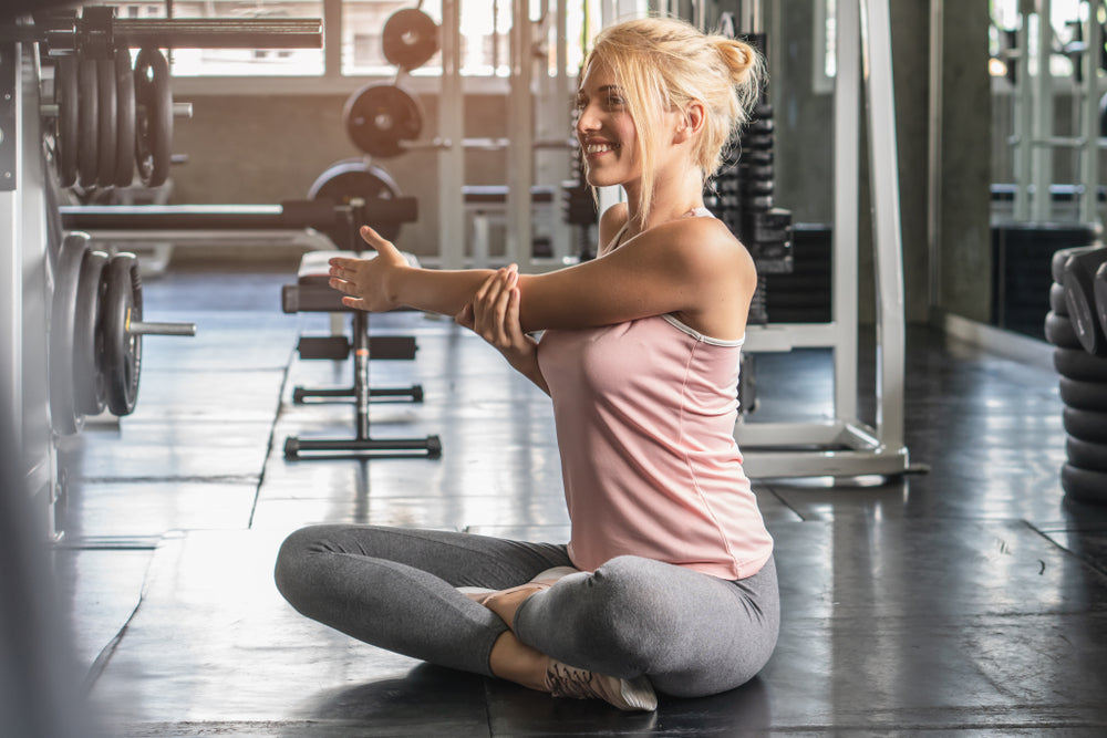 woman stretching shoulder to prevent pain
