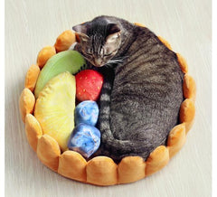 Cat sleeping inside a plush fruit tart cat bed