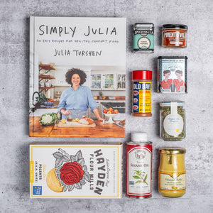 Simply Julia cookbook on top of grey concrete background surrounded by jarred, boxed, and bottled ingredients