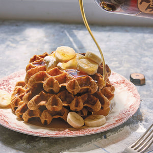 Waffles topped with bananas and a long pour of maple syrup