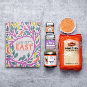 East cookbook on grey background surrounded by packaged ingredients