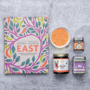East cookbook on a grey background with a few packaged ingredients set beside it