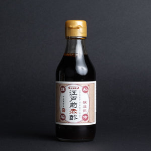 A bottle of Akasu Red Vinegar on a black background