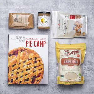 Pie Camp cookbook on a grey background with assorted packaged baking ingredients laid out around it