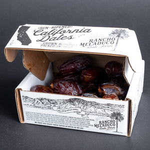 A box of Rancho Meladuco dates in a white cardboard box open slightly and showing the dates inside