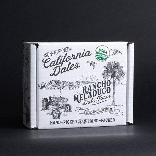 A box of Rancho Meladuco dates in a white branded cardboard box on a black background