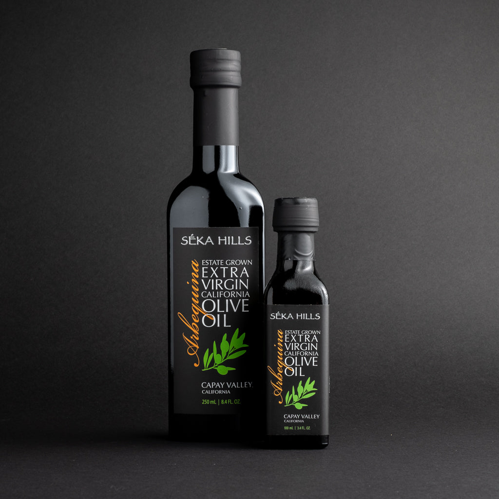 Seka Hills Extra Virgin Olive Oil bottles in two sizes against a black background