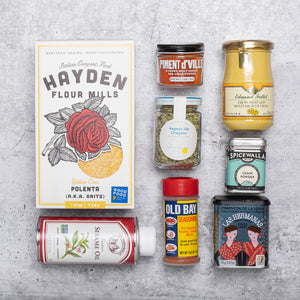 An assortment of pantry products laid on top of a grey concrete background