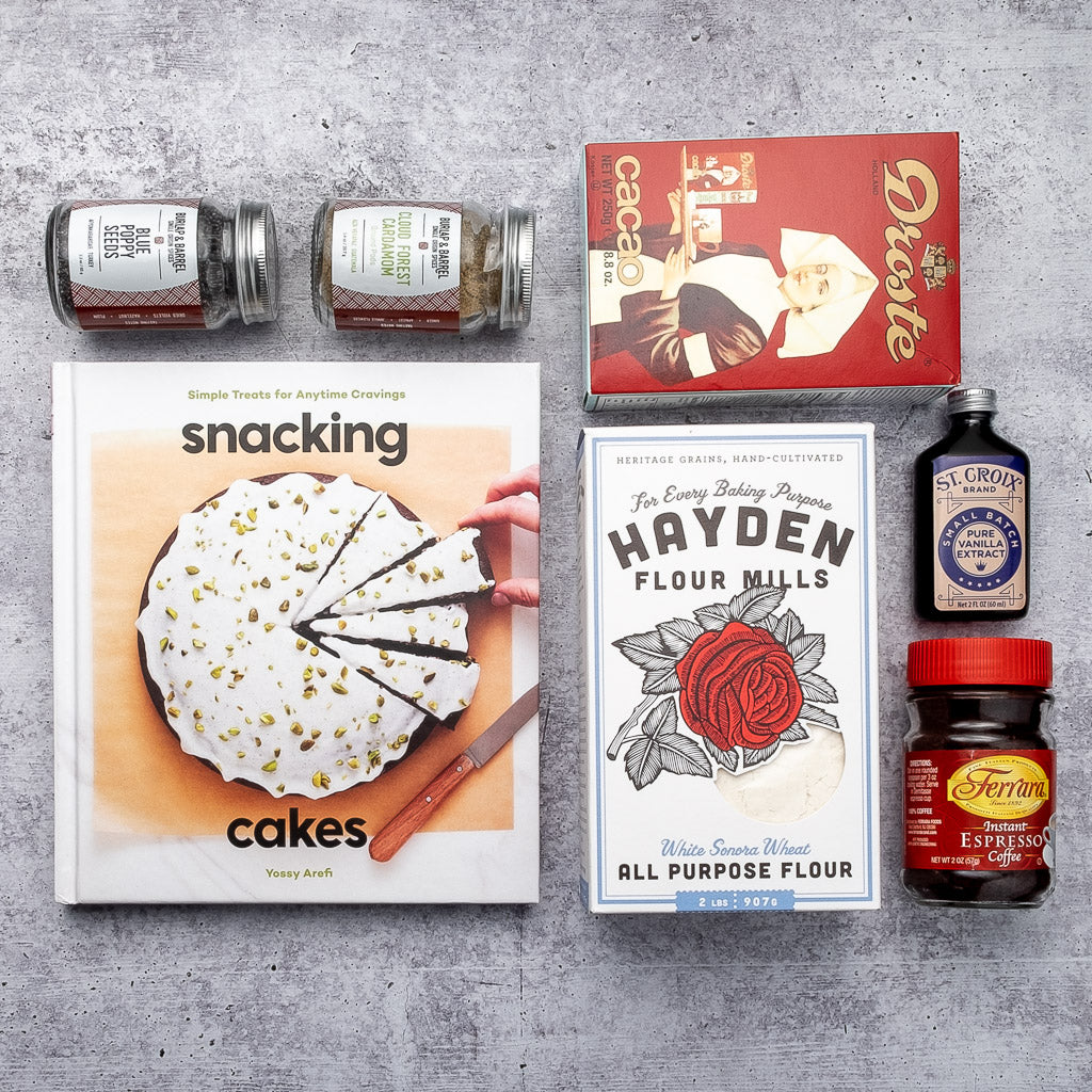 Snacking Cakes cookbook and an assortment of baking ingredients