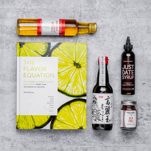The Flavor Equation cookbook with an assortment of ingredients laid flat: Mustard Seed Oil in a glass bottle, Japanese Soy Sauce in a glass bottle, Just Date Syrup, Burlap & Barrel Silk Chili