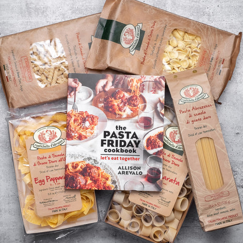 Pasta Friday cookbook atop an assortment of packaged pasta from Rustichella d'Abruzzo
