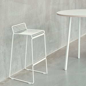 The absence of superfluous details in the Hee Bar Stool seems even more pronounced by its height and the presence of long slender legs. The ultimate in elemental design, this versatile bar/counter stool has a simple, uncluttered expression with excellent stability. Stackable and weather-proof, the Hee Bar Stool can be used in outdoor surroundings, as well as inside restaurants, bars and in the home.