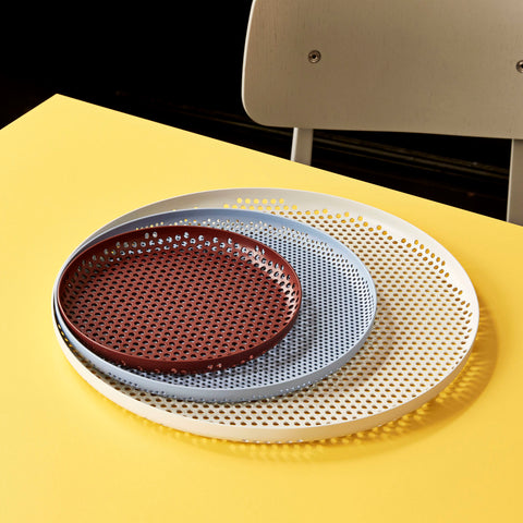 Lex Pott for HAY's round Perforated Tray uses hundreds of tiny circular holes to create a structured effect. The round tray features curved, slightly raised sides for extra stability when carrying or displaying items. Made in aluminium in three sizes, and available in a variety of different colours.
