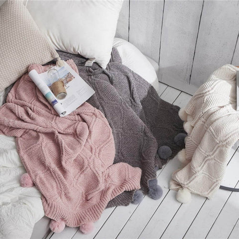Three hygee knit pom-pom blankets laid out with pillows, a magazine, and a water bottle