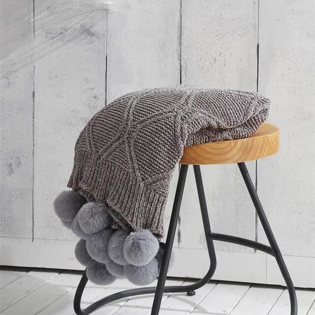A gray hygee knit pom-pom blanket on a stool