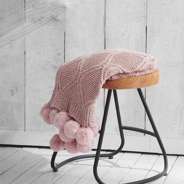 A pink hygee knit pom-pom blanket on a stool