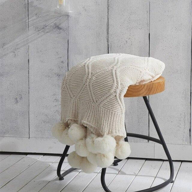 A white hygee knit pom-pom blanket on a stool
