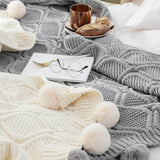 A white and a gray hygee knit pom-pom blanket on a bed with a mug