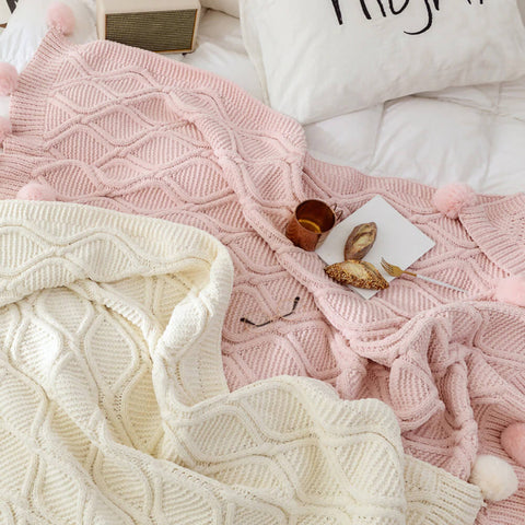 A white and a pink hygee knit pom-pom blanket on a bed with a mug