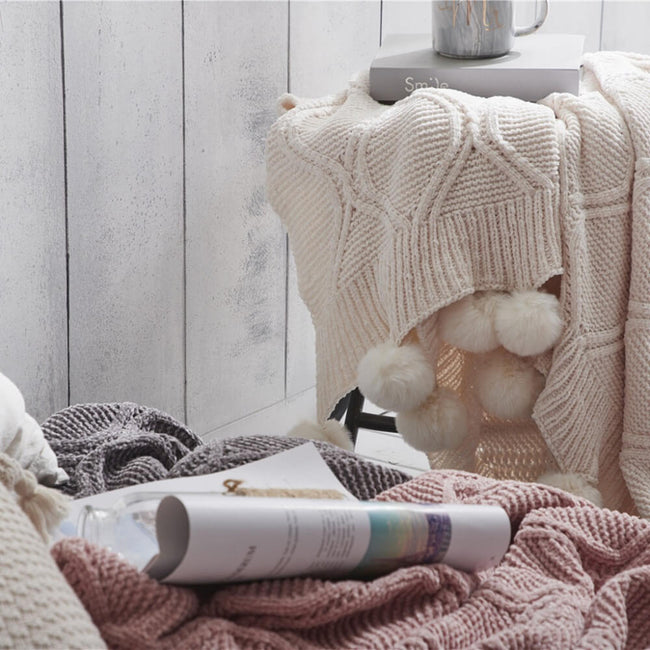 Three hygee knit pom-pom blankets, white blanket on stool and other two on bed with magazine