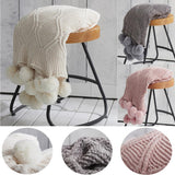Three hygee knit pom-pom blankets on stools