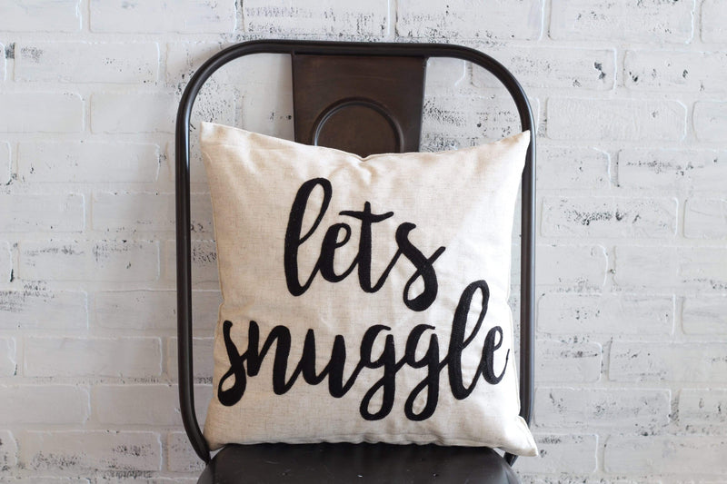 """Lets Snuggle"" black lettering on white pillow"