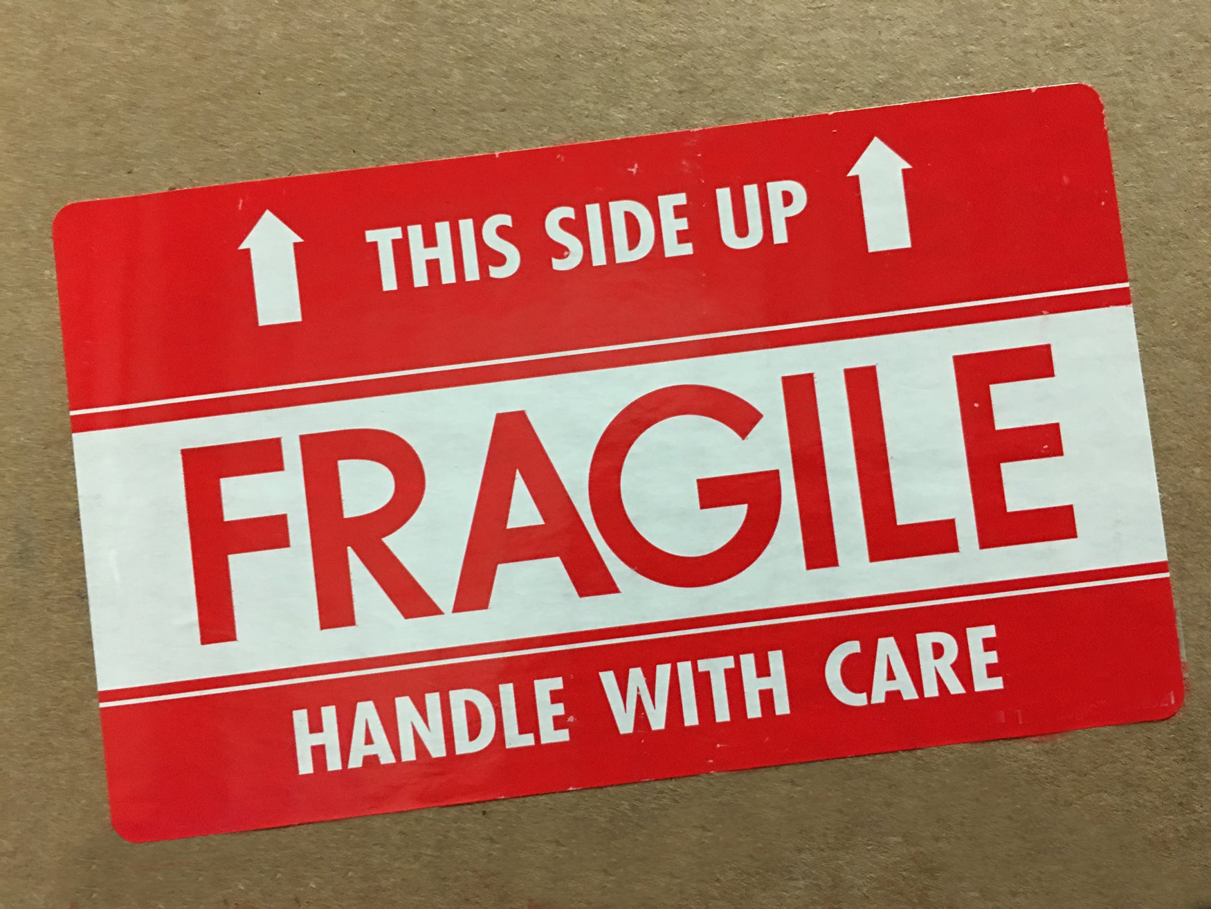 Detail of a box with a FRAGILE - This Side Up sticker