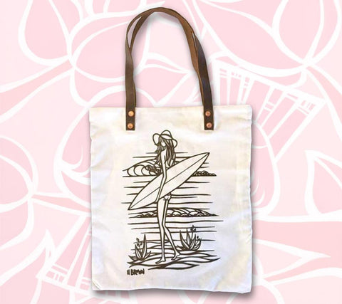 "The ""Sandy"" Tote Bag by Heather Brown features a girl walking along a tropical beach with her surfboard, heading towards a day of epic waves."