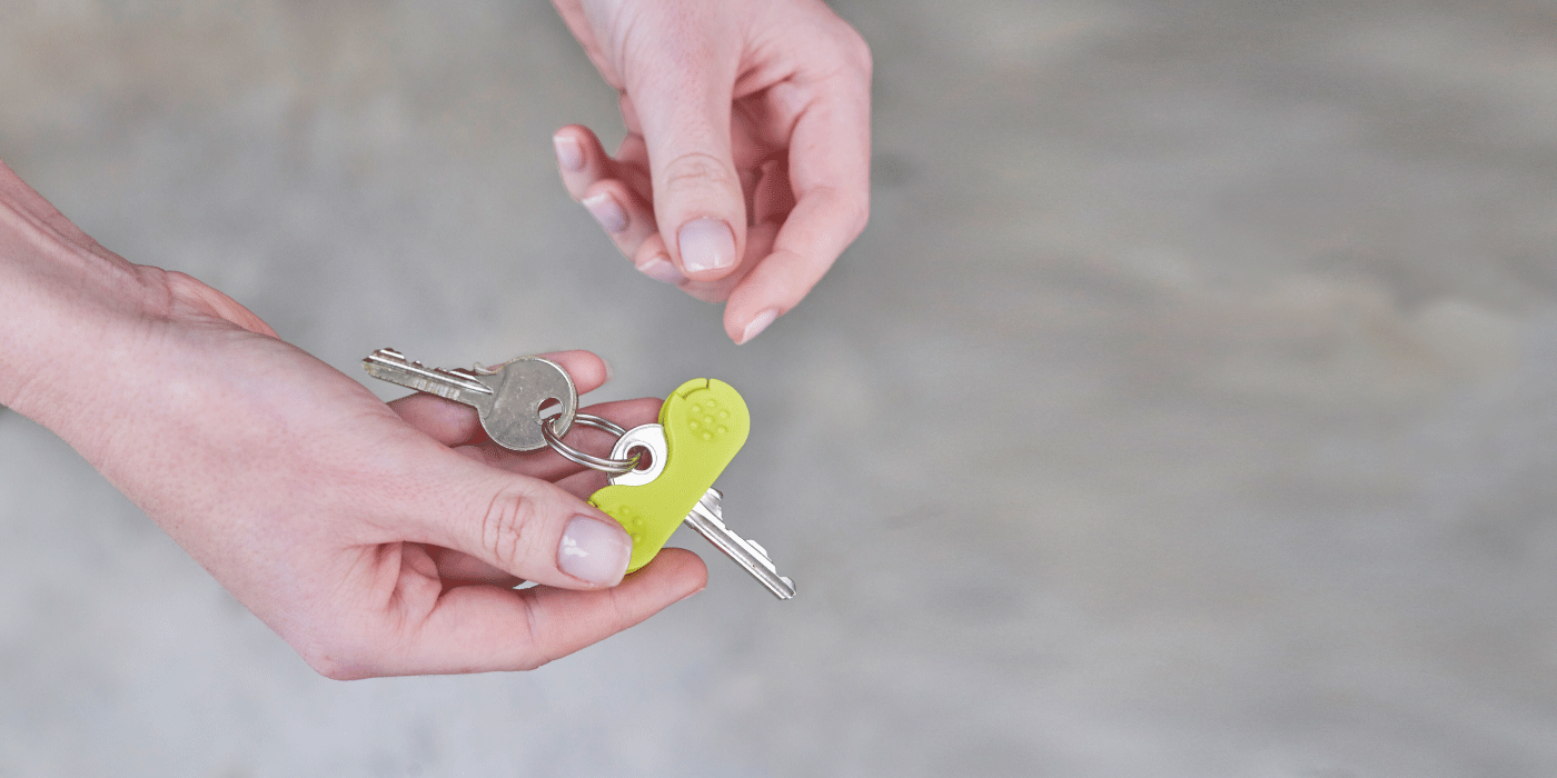 Two hands holding a green keywing key turner aid on a key.