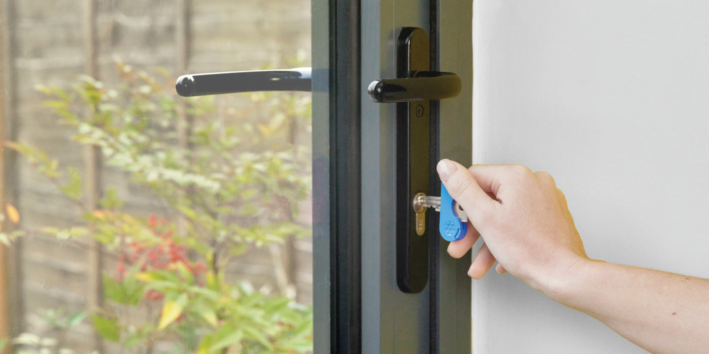 The keywing key turner arthritis aid in blue being used in a hand on a grey door.