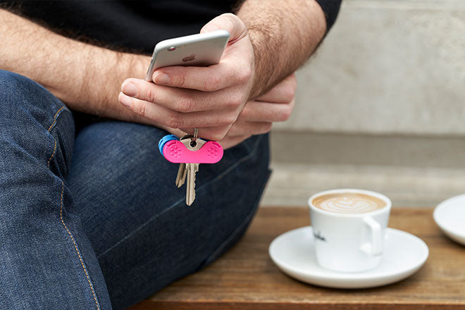 A pink keywing key turner rheumatoid arthritis product on a finger with phone and coffee.