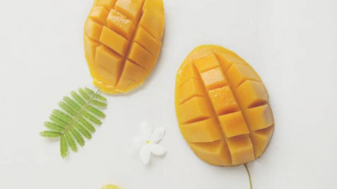 Two cut mangos on a white background