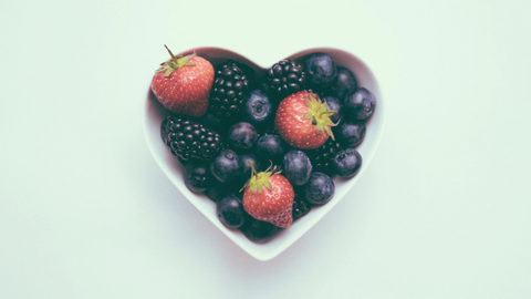 A heart shaped white bowl with berries on a white background