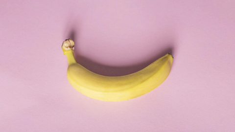 One banana on a pink background