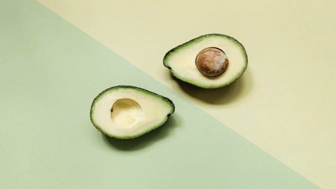 A cut avocado an a green and yellow background