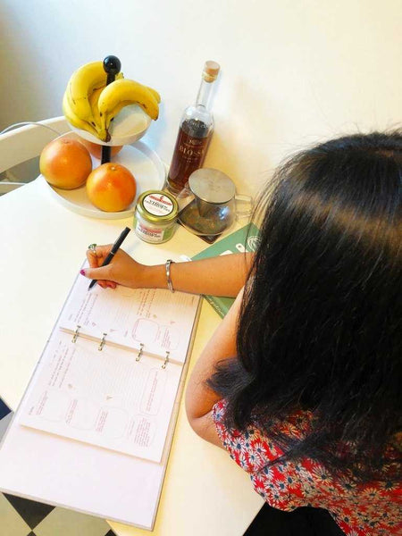 A woman writing journal on a kitchen table