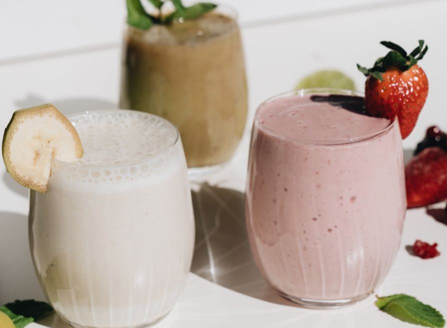 Three different smoothies with fruits on the side