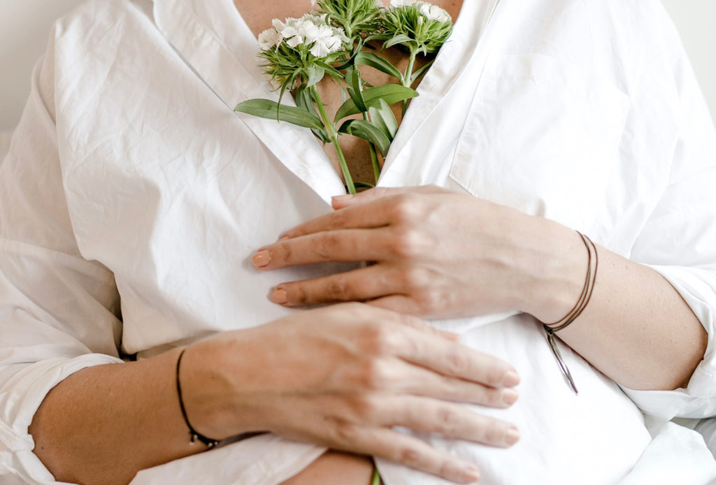 Pregnant woman in white shirt holding a bunch of white flower