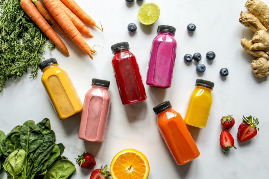 A few bottles of colorful smoothies surrounded by fruits and vegetbles